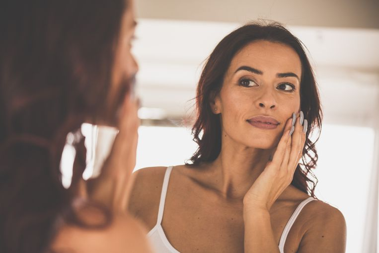 Portrait of a beautiful woman doing her everyday beauty routine in front of mirror. Beeld Getty Images