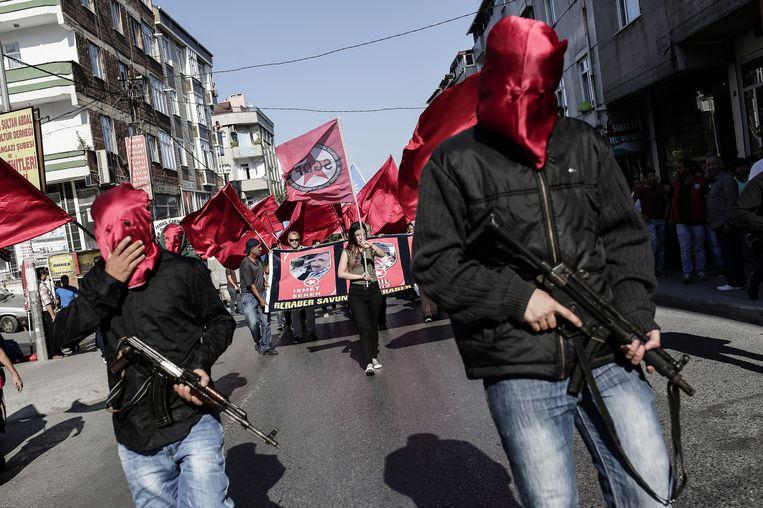 Gewapende aanhangers van de SGDF escorteren in Istanbul de kisten met slachtoffers die omkwamen in Suruç. Beeld afp