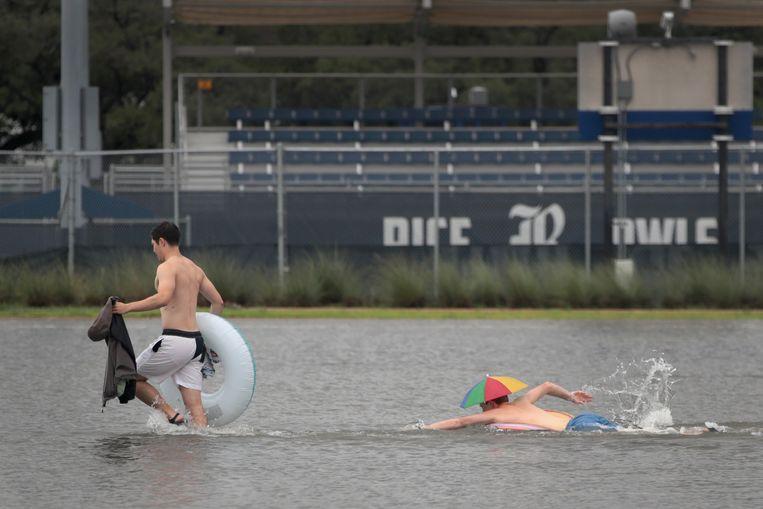 Studenten van de Rice University in Houston maken van de nood een deugd en brengen zichzelf met zwembanden in veiligheid via een ondergelopen parkeerterrein op hun campus. Beeld Getty Images