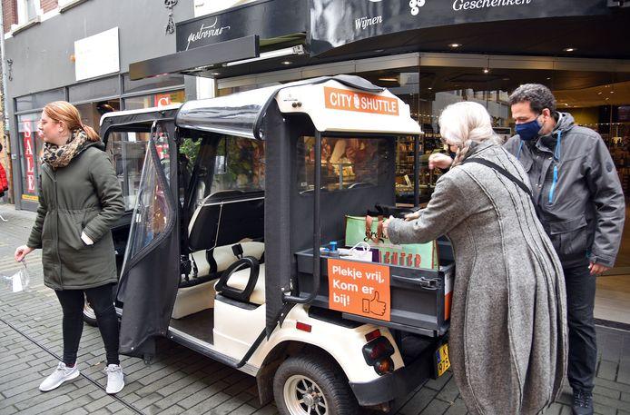Jolien Dekker en Roel de Haay laden in de Noordstraat hun boodschappen in de city shutle, links chauffeuse Anne Brouwer.