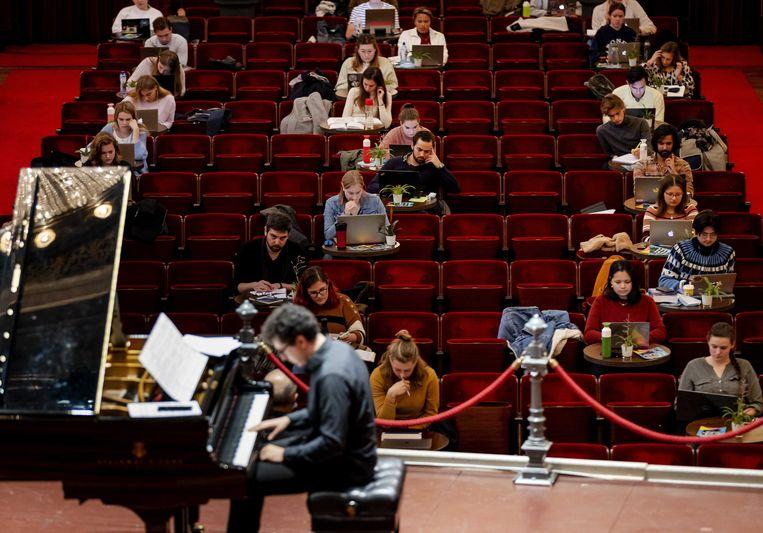 Studenten studeren in de grote zaal van het Concertgebouw onder het genot van klassieke muziek. Beeld ANP
