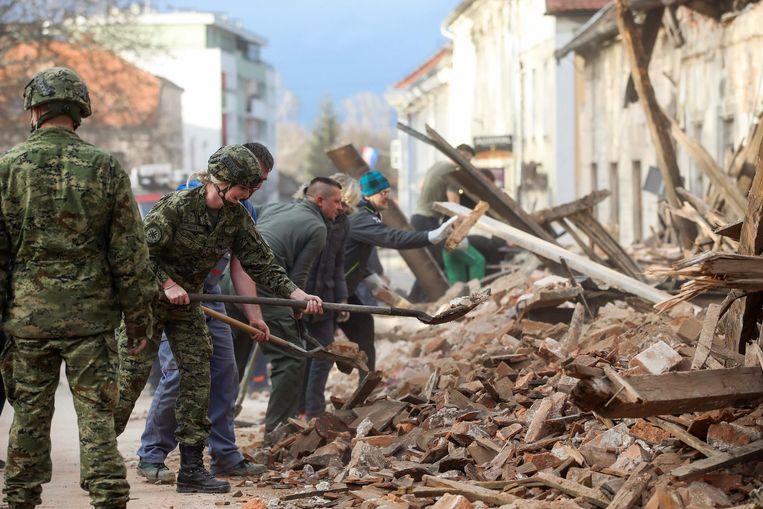Kroatische soldaten en burgers ruimen puin in Petrinja. Beeld AFP