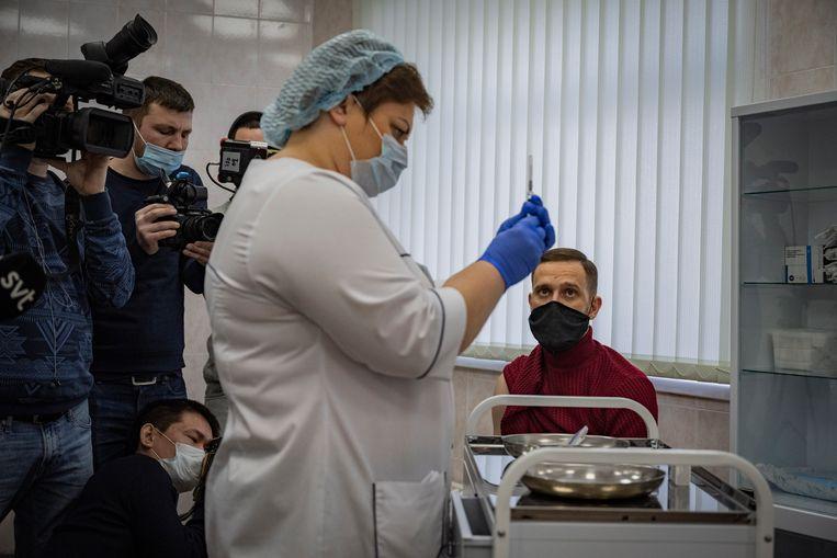 Een Russische zorgmedewerker maakt een injectie klaar om het Spoetnik V-vaccin in de bovenarm van een arts te spuiten. Beeld Yuri Kozyrev /  Noor