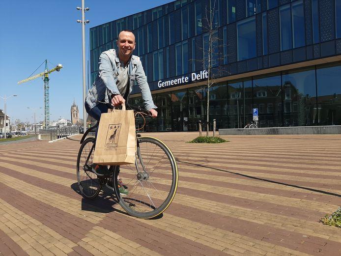 Ray van Uffelen maakt van de nood een deugd door bestellingen op de fiets te bezorgen.