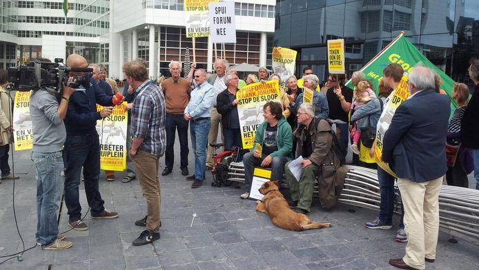 HSP-lijsttrekker Joris Wijsmuller (links op de rug gezien) tijdens zijn verkiezingscampagne tegen het Spuiforum. nu verdedigt hij als wethouder het vernieuwde Spuiforumplan.