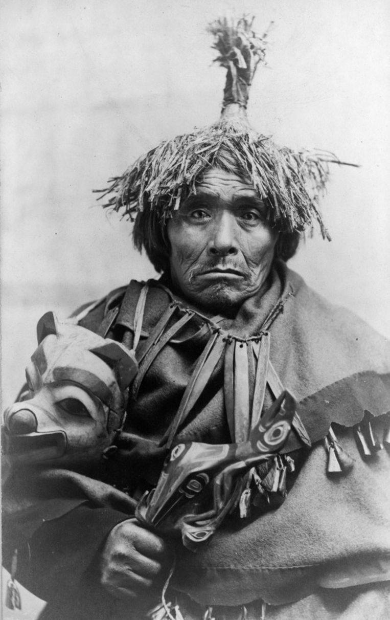 Tlingit-man met ravenrammelaar in Zuid-Oost Alaska, circa 1899.  Beeld Alaska Native Collections