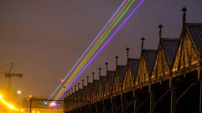 Laserstralen verbinden M HKA en Het Steen met regenboogvlag