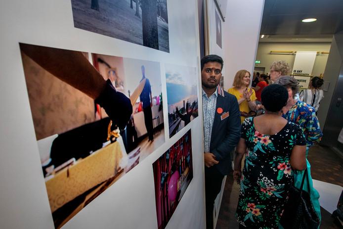 Vluchteling Sansigithan poseert bij de foto's die hij maakte over zijn leven in Nederland.