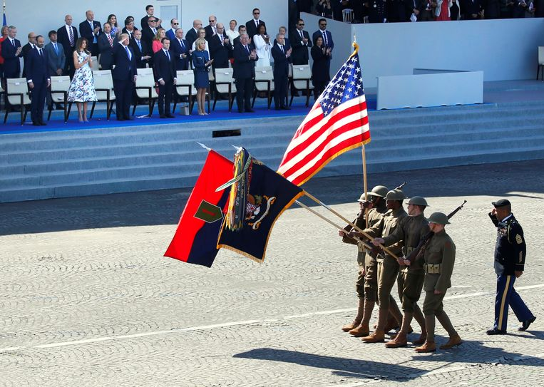 Amerikaanse soldaten wandelen langs de Franse president Emmanuel Macron en de Amerikaanse president Trump tijdens de nationale Franse feestdag op 14 juli 2017. Beeld REUTERS