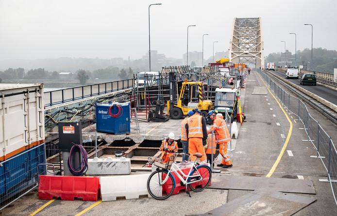 Bouwvakkers werken aan de Waalbrug. Het verkeer rijdt aan beide kanten langs.