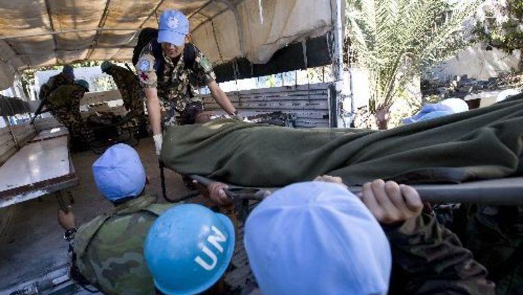 VN-medewerkers laden een gewonde in een gereedstaande vrachtwagen in Port-au-Prince. De VN verloren zelf ook veel personeel door de aardbeving die Haïti op 12 januari trof. ANP Beeld