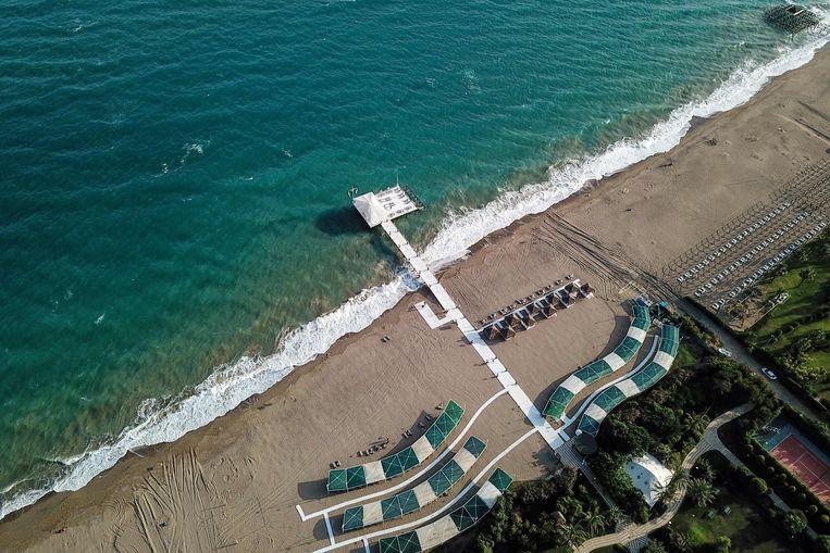 Eind juni, een strand in Antalya. Normaal moet je er 's ochtends heel vroeg bij zijn om een plekje te bemachtigen. Nu ligt het toerisme zo goed als stil. Beeld AFP