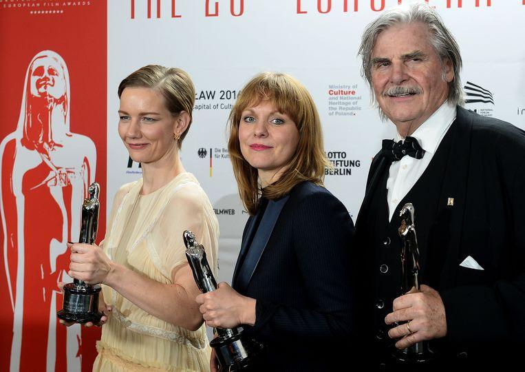 De Duitse actrice Sandra Hüller, regisseuse Maren Ade en de Oostenrijkse acteur Peter Simonischek met hun awards. Beeld AFP