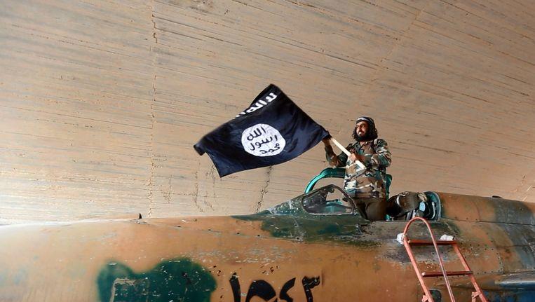 Een strijder van Islamitische Staat wappert met de vlag van de terreurorganisatie nadat zij de luchtmachtbasis Tabqa in Syrië hebben veroverd. Beeld ap