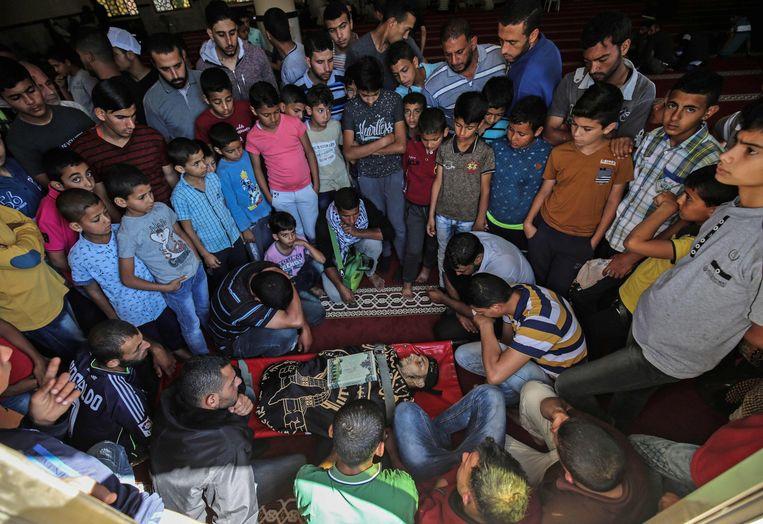 Palestijnen rouwen bij het lichaam van een man die werd gedood bij de grens tussen Gaza en Israël. Beeld AFP