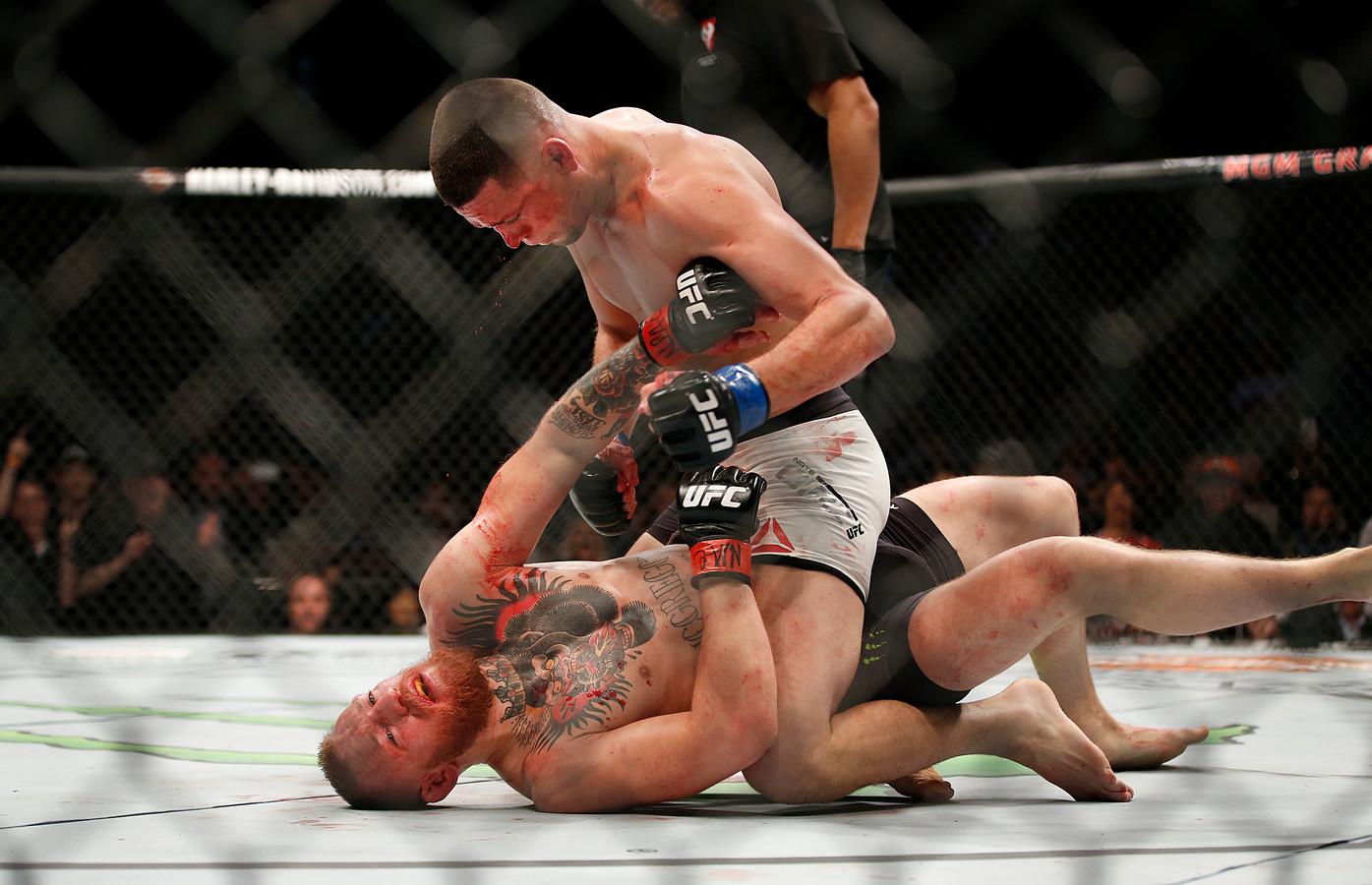 Nate Diaz, zittend,  in gevecht met Conor McGregor tijdens hun UFC 196 weltergewicht wedstrijd op zaterdag 5 maart 2016 in Las Vegas.