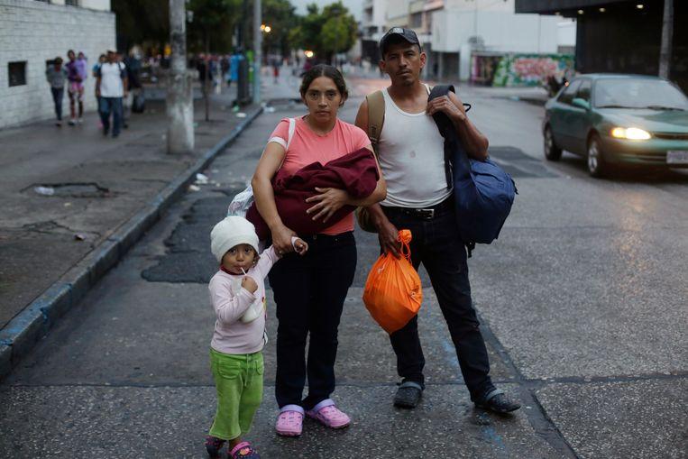 Klaar om te vertrekken vanuit de Hondurese hoofdstad Tegucicalpa: Keidy Arreaga met haar dochter van twee maanden op de arm, haar dochter Keidy van 3 jaar en haar broer Wilver (32). Ze willen naar de VS, op zoek naar een beter leven. Beeld AP