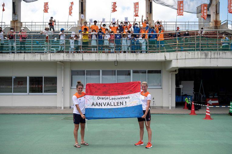 Danielle van de Donk (links) en Jackie Groenen poseren met een vlag die ze hebben gekregen van kinderen uit  Kamogawa, waar ze trainen tijdens de Olympische Spelen Beeld AFP
