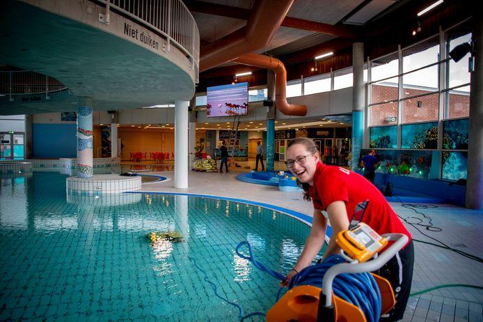 Maandagmiddag: medewerkster Ilona Boom maakt de zwembadvloer schoon voor de heropening van dinsdag 3 december. Linksboven het grote scherm, rechts achter Boom de nieuwe peuter- en kleuterhoek.