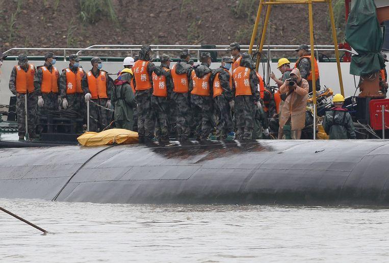 Reddingswerkers staan op de romp van het gezonken schip. Beeld reuters