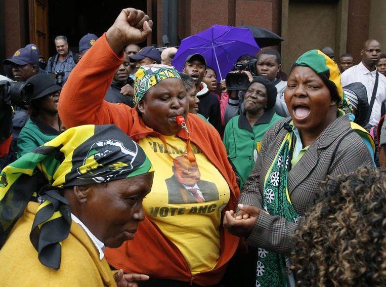 Buiten het gerechtsgebouw zingen leden van het ANC (African National Congress) voor de rechten van de vrouw. Beeld REUTERS