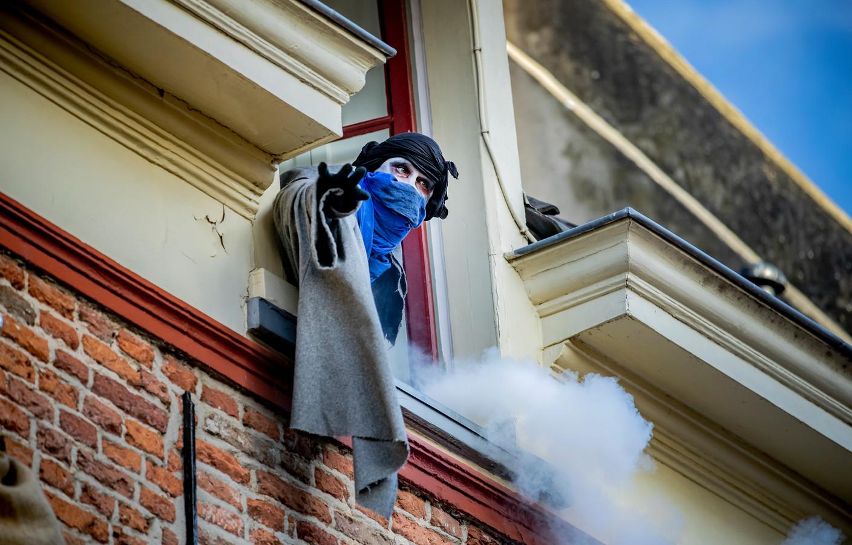 De geest hangt uit het raam en roept Scrooge tot zich.