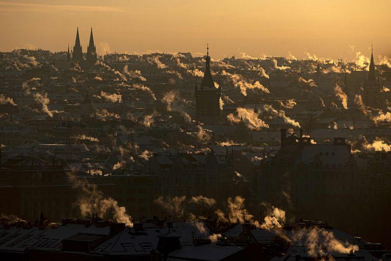 Er komt rook uit de schoorstenen van de daken in het centrum van Praag. Dit was op 12 februari, tijdens de zonsopgang. Het was toen min 17 graden Celsius.  Beeld AFP