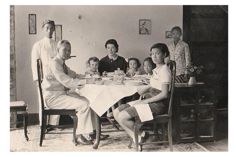 De grootouders van de auteur, Carl Braun en Angelique Plas met moeder Mea Braun (witte strik in het haar) rond de tafel in Solo, Java, in de jaren dertig. Beeld null