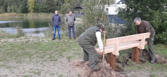 Twee boswachters van Staatsbosbeheer plaatsen de bank voor Loes van Geffen. Echtgenoot Jan en zoon Mark van Geffen kijken toe.