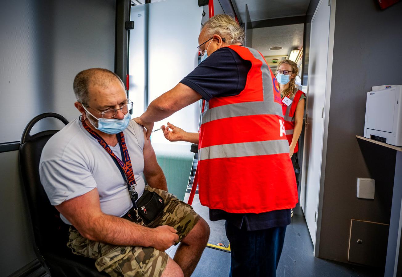 Medewerkers van de GGD aan het werk in een prikbus. Die wordt ingezet om de vaccinatiegraad te verhogen.