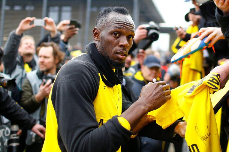 Usain Bolt staat na zijn atletiekcarrière geregeld op een voetbalveld. Hier signeert hij voetbalshirts van fans na een training met Borussia Dortmund. Beeld REUTERS