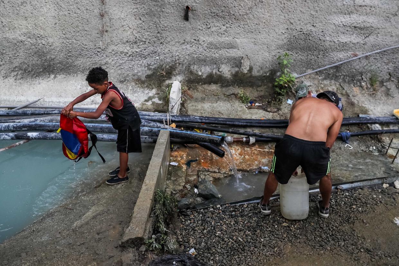 Bewoners halen water bij een verlaten gebouw in Caracas. Beeld EPA