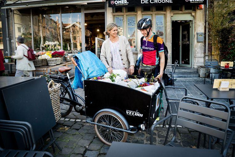 Colette Van Vlaenderen en bakfietskoerier Peter Aernout bij bloemist Volckaert. Beeld Eric de Mildt