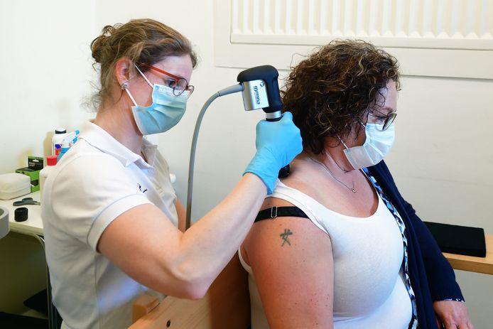 Ilse Krijgsman (r) wordt behandeld door fysiotherapeut Marieke van Zuilichem voor haar nek, rug- en schouderklachten als gevolg van het thuiswerken. Een trilapparaat moet de kalk op de spiervezels in haar schouder vergruizen.