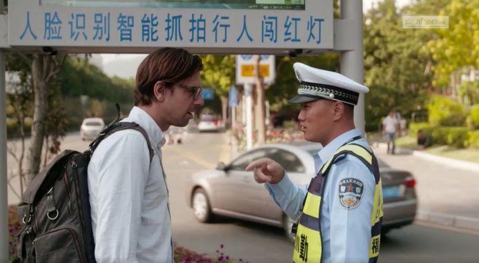 Documentairemaker Ruben Terlou spreekt in de miljoenenstad Shenzhen met een politieagent. Op een waarschuwingsbord staat uitgelegd dat gezichtsherkenning wordt gebruikt aan de verkeerslichten.