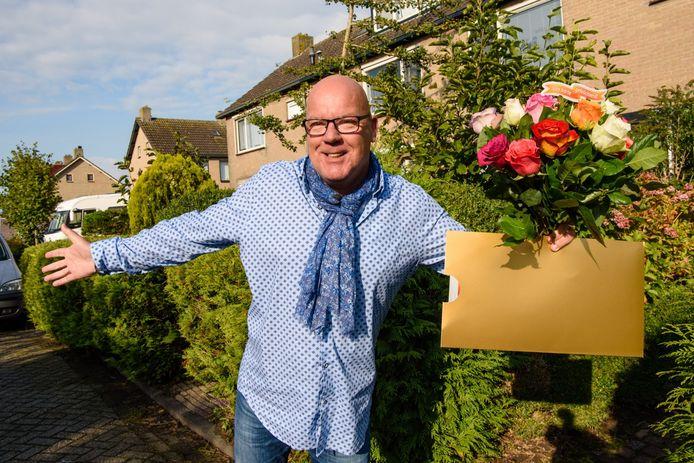 Postcode Loterij-ambassadeur Gaston met cheque en bloemen.