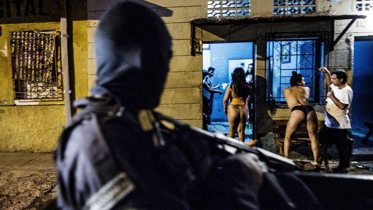 Een politie-eenheid staat voor een bordeel in San Salvador. De straten van de hoofdstad zijn 's avonds vrijwel verlaten uit angst voor het geëscaleerde geweld. Beeld Manu Brabo/AP