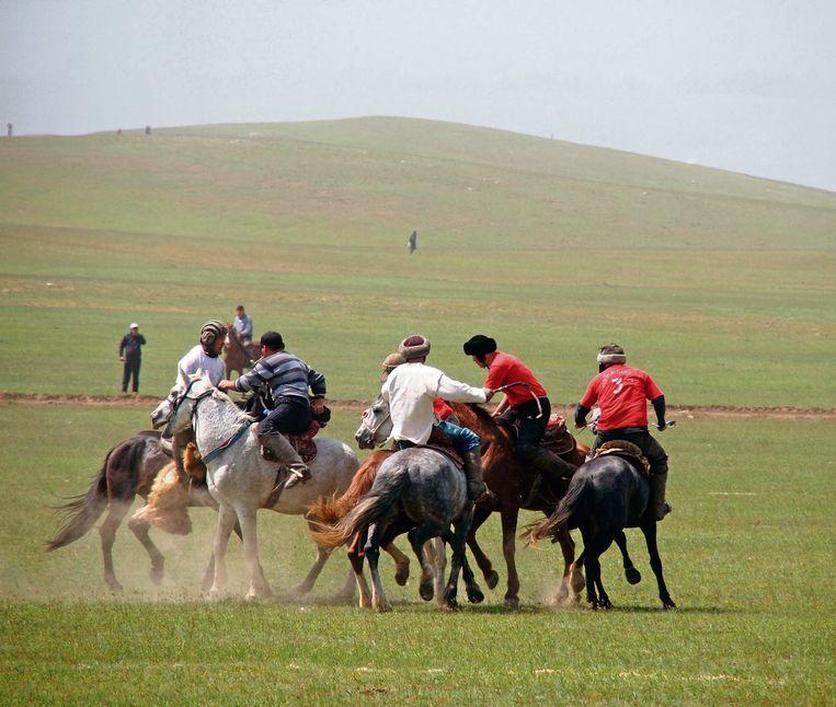 Kokpar, Kazachs polo.Het geitenkarkas waar het om draait, bungelt aan het meest linkse paard.  Beeld rv Erika Fatland
