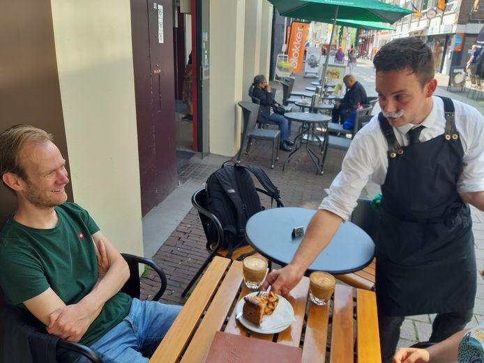 Een medewerker van Walt in Arnhem serveert koffie met appeltaart, zonder mondkapje maar mét plaksnor.