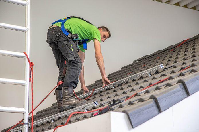Zonnepanelenleverancier Zonneplan in Zwolle leidt met eigen academy monteurs op voor het plaatsen van zonnepanelen. In een hal zijn meerdere daken nagebouwd, waarop monteurs oefenen.