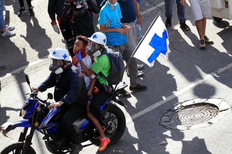 Een gewonde demonstrant wordt weggevoerd door vrijwillige hulpverleners. Beeld reuters