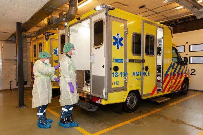 Medewerkers van de ambulancedienst Zuid-Holland Zuid in beschermende kleding vanwege het coronavirus.