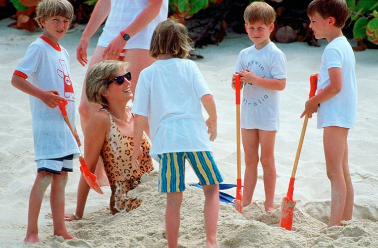 Diana wordt begraven in het zand door haar zoons  tijdens een vakantie. Beeld Tim Graham Photo Library via Get