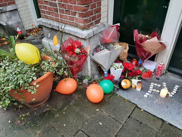 Bloemen en kaarsen voor de deur.