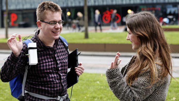 Tim in 't Veld met zijn bril die gezichten herkent. Het witte doosje op zijn schouder is een geluidsapparaat dat de naam van de persoon uitspreekt die 'gezien' wordt.