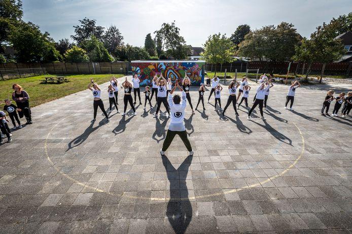 Dansvereniging T-Force oefent hun dinnershow op het schoolplein van basisschool de Wereldwijzer.