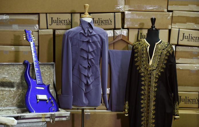 De geveilde blauwe cloud-gitaar van Prince, samen met enkele kledingstukken van de artiest.