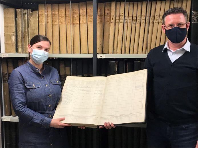 Leen Breyne en schepen Kurt Himpe met een boek uit het stadsarchief.