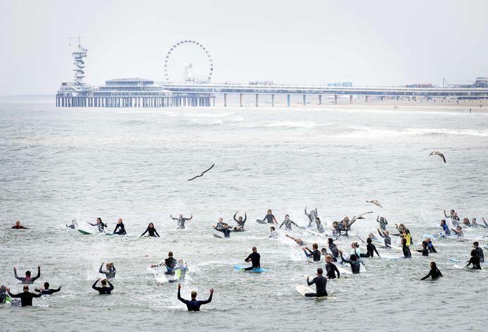 Surfers nemen met een zogenaamde paddle out afscheid van hun vrienden die in mei zijn omgekomen. Metershoog zeeschuim kostte vijf surfers het leven.