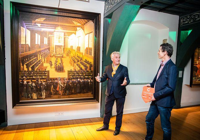 Museumdirecteur Peter Schoon (links) laat het schilderij van Pouwel Weytsa de Jonge van de Synode zien aan zijn collega, Teus Eenkhoorn van het Nederlands Openluchtmuseum in Arnhem.